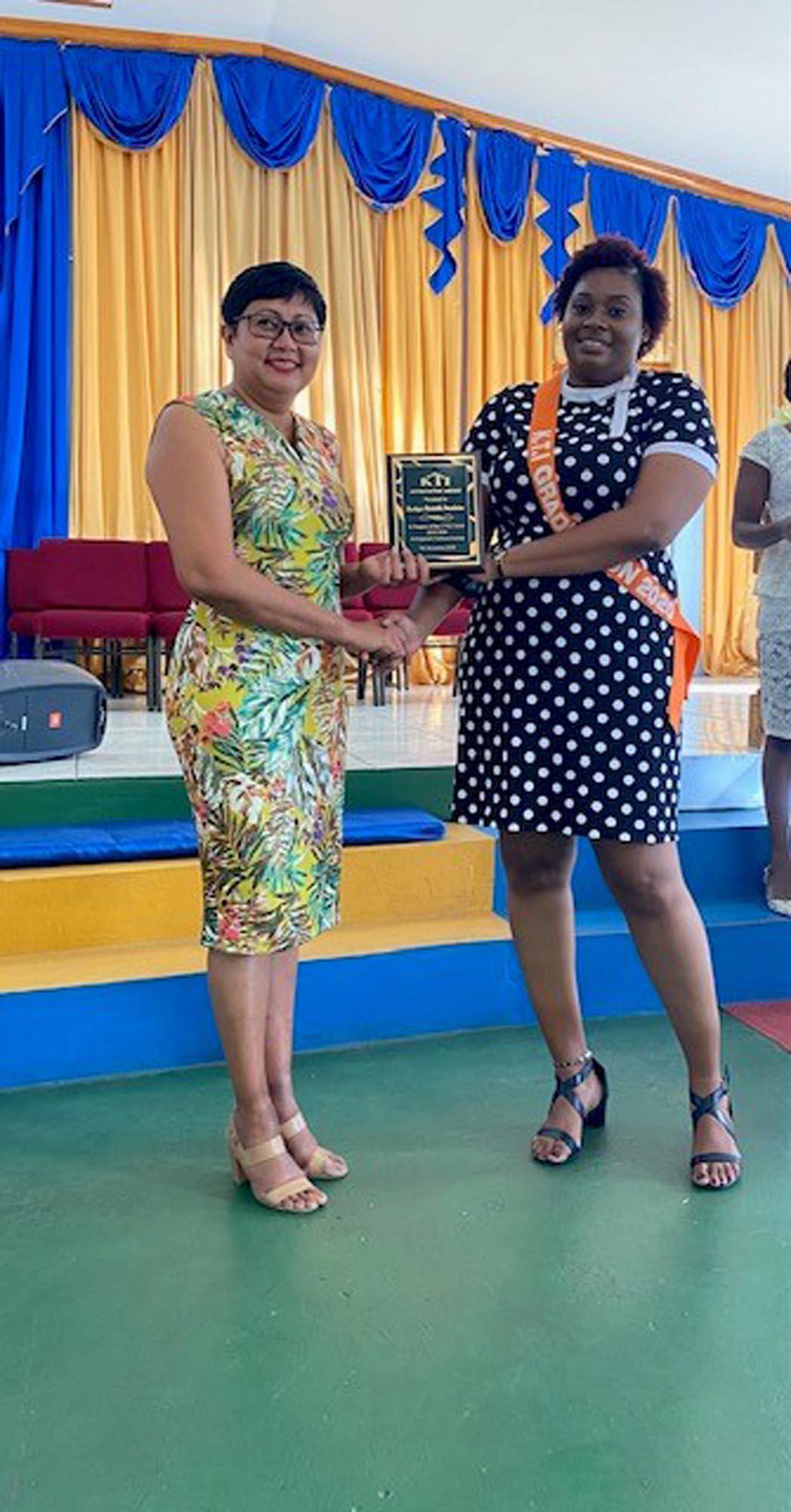 Dularie Malcolm (MCF Project Director) receiving MCF Appreciation Award from MCF Bursary Recipient